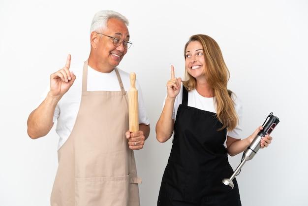 Casal de chefs de meia-idade isolado em um fundo branco com a intenção de descobrir a solução enquanto levanta um dedo