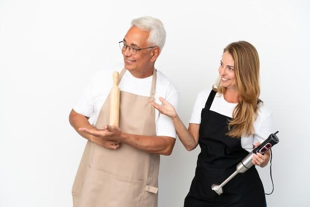 Casal de chefs de meia-idade isolado em um fundo branco estendendo as mãos para o lado para convidar para vir