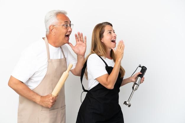 Casal de chefs de meia-idade isolado em um fundo branco gritando com a boca bem aberta para a lateral