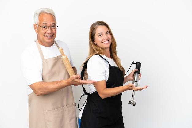 Casal de chefs de meia-idade isolado no fundo branco apontando para trás e apresentando um produto