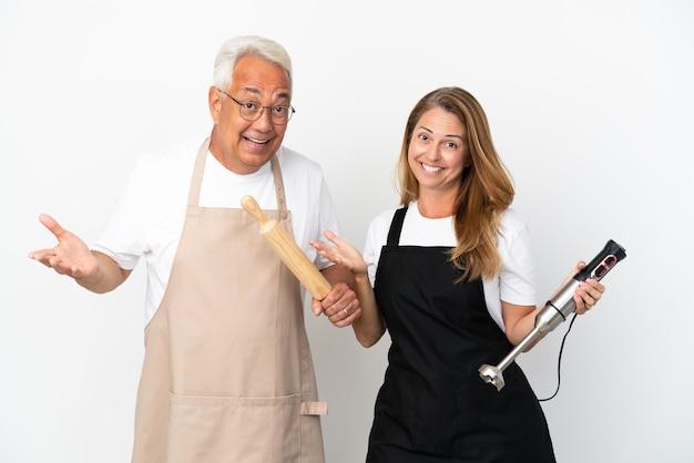 Casal de chefs de meia-idade isolado no fundo branco com dúvidas enquanto levanta as mãos e os ombros