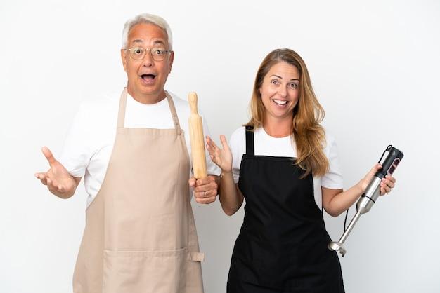 Casal de chefs de meia-idade isolado no fundo branco com expressão facial de surpresa e choque