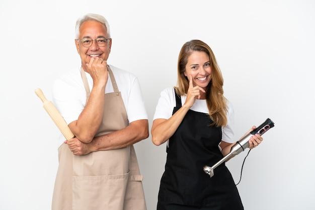 Casal de chefs de meia-idade isolado no fundo branco e sorrindo com uma expressão doce