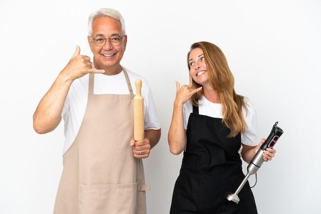 Casal de chefs de meia-idade isolado no fundo branco fazendo gesto de telefone. ligue-me de volta sinal