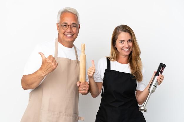 Casal de chefs de meia-idade isolado no fundo branco fazendo um gesto de polegar para cima com as duas mãos e sorrindo