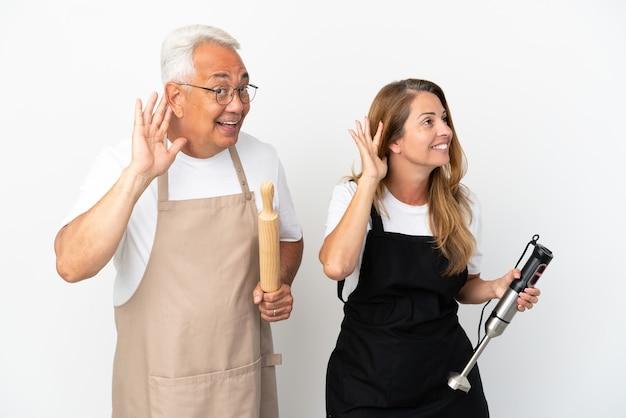 Casal de chefs de meia-idade isolado no fundo branco ouvindo algo colocando a mão na orelha