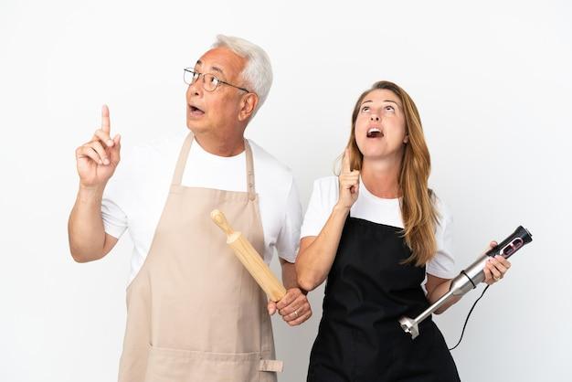 Casal de chefs de meia-idade isolado no fundo branco pensando em uma ideia apontando o dedo para cima
