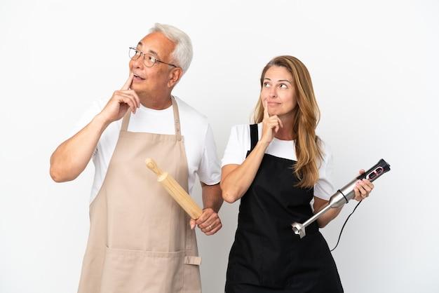 Casal de chefs de meia-idade isolado no fundo branco pensando em uma ideia enquanto olha para cima