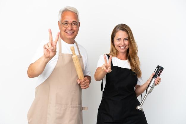 Casal de chefs de meia-idade isolado no fundo branco sorrindo e mostrando sinal de vitória