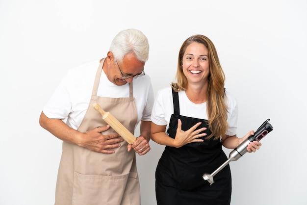 Casal de chefs de meia-idade isolado no fundo branco sorrindo muito enquanto colocava as mãos no peito