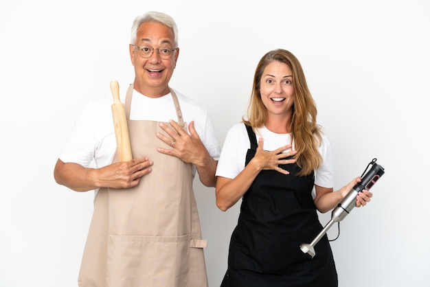 Casal de chefs de meia-idade isolado no fundo branco surpreso e chocado ao olhar para a direita