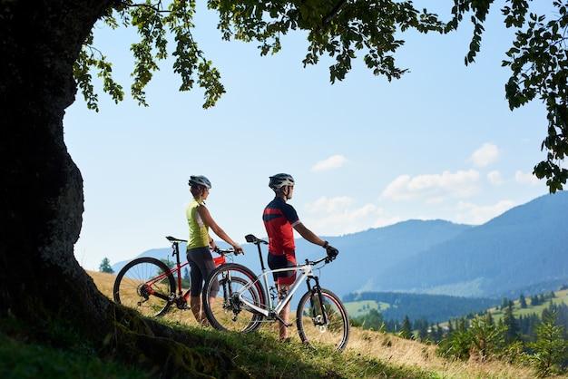 Casal de ciclistas admirando a vista