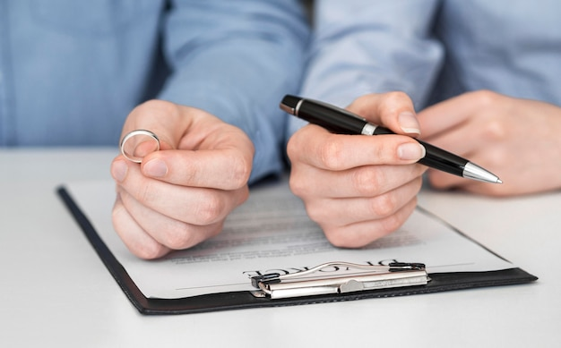 Casal de close-up, assinando contrato de divórcio