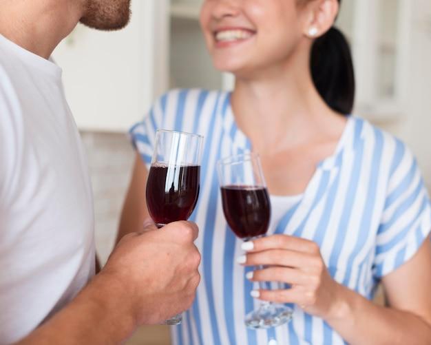 Casal de close-up com copos de vinho