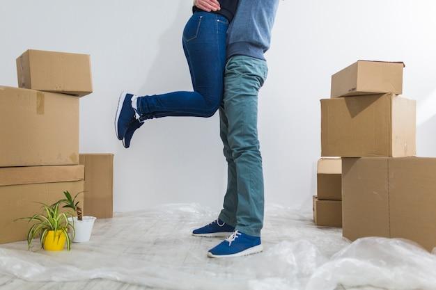 Casal de colheita abraçando perto de caixas de papelão