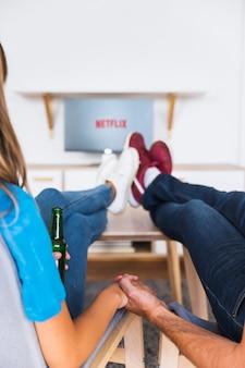 Casal de colheita com cerveja, desfrutando de programas de tv