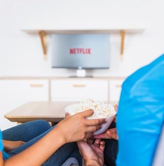 Casal de colheita comendo pipoca e assistindo a série de tv