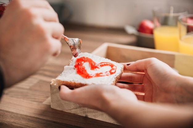 Casal de colheita fazendo torradas com geléia