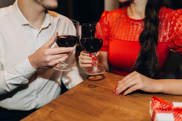 Casal de colheita tilintando com copos de vinho