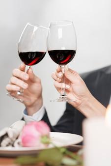 Casal de colheita tinindo com copos de vinho