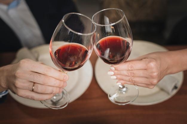 Casal de colheita tinindo com vinho