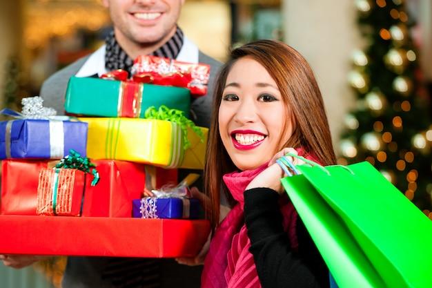Casal de compras de natal com presentes no shopping