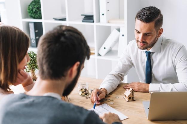 Casal de consultoria com agente imobiliário