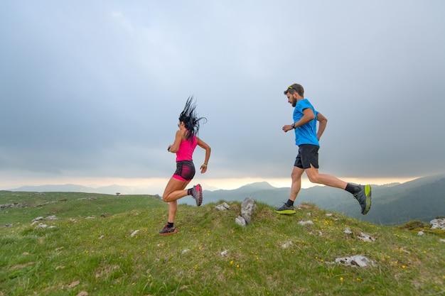 Casal de corredores de atletas de montanha homem e mulher em ação