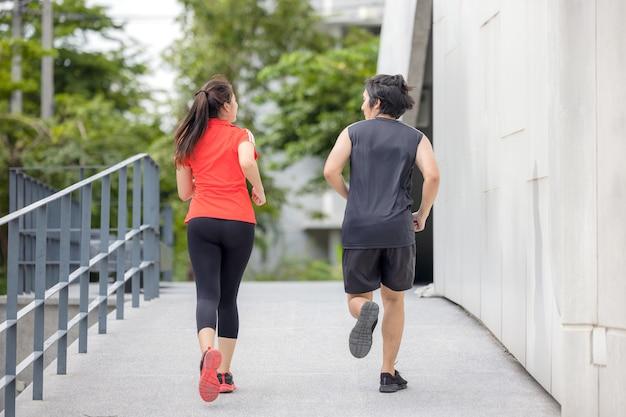 Casal de corrida se exercitando na cidade em uma foto de esporte ativo em uma cidade urbana, com prédios ao fundo