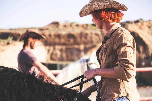 Casal de cowboy moderno cavalga juntos. um homem e uma mulher com dois cavalos. imagem de filtro quente para estilo de vida alternativo e conceito de trabalho ou atividade ao ar livre. sentindo a natureza
