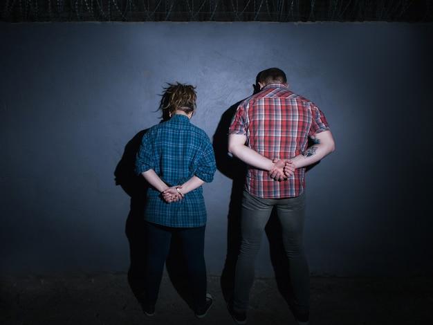 Casal de criminosos presos. parceiros no crime. detenção de pessoas irreconhecíveis à noite em fundo azul, jovens com as mãos atrás das costas, conceito de prisão