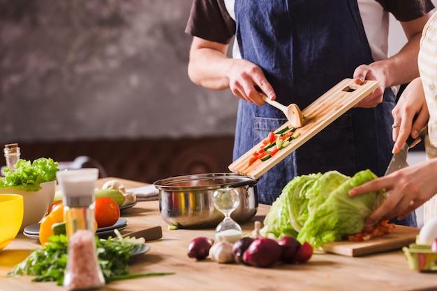 Casal de culturas cozinhar salada juntos