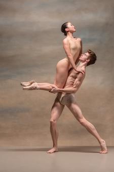 Casal de dançarinos de balé posando sobre espaço cinza