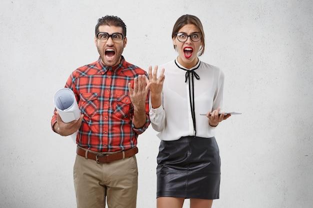 Casal de designers assediados e furiosos gesticulam perplexos e gritam em pânico