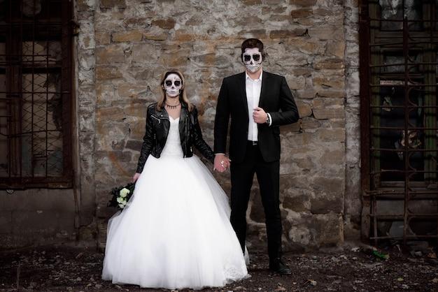 Casal de dia das bruxas. vestida com roupas de casamento romântico zumbi