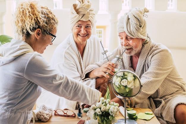 Casal de dois idosos desfrutando de um spa e tratamento de massagem junto com uma assistência ajudando-os - bebendo coquetéis e se divertindo sorrindo