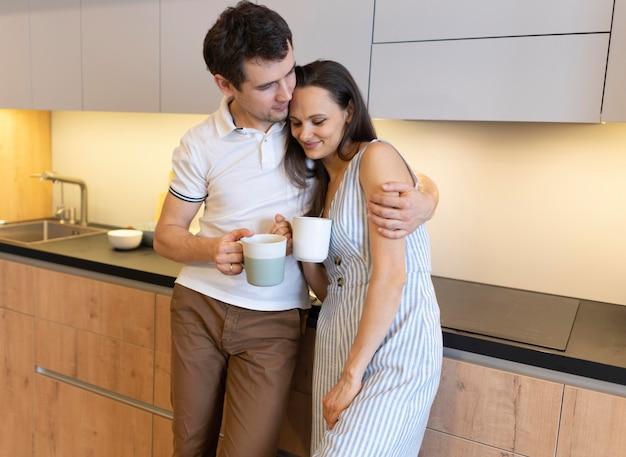 Casal de dose média segurando copos