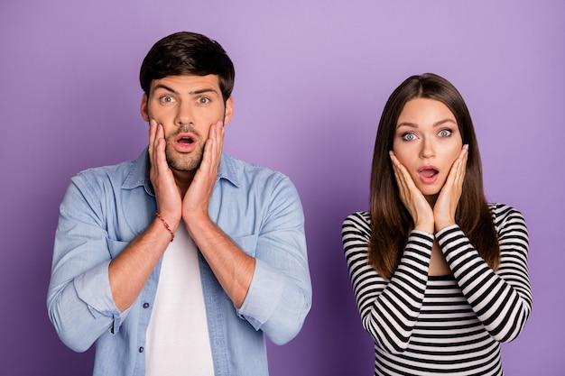 Casal de duas pessoas segurando os braços nas bochechas ouve notícias negativas horríveis usam roupas casuais elegantes na parede de cor roxa pastel isolada