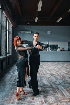 Casal de elegância no treinamento de dança ballrom em sala de aula. parceiros masculinos e femininos em pares profissionais dançando no estúdio