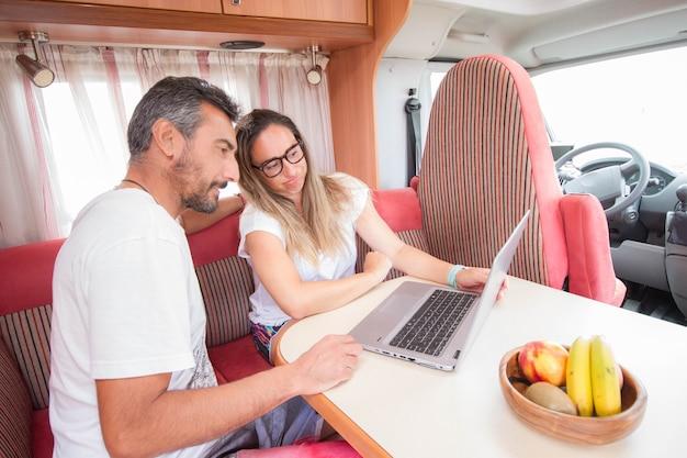 Casal de empreendedores teletrabalhando em um motorhome ou campervan como escritório