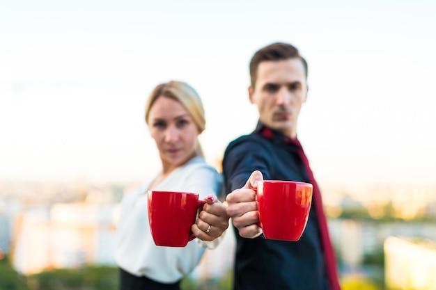 Casal de empresários, homem atraente morena e mulher bonita loira ficar no telhado e beber café