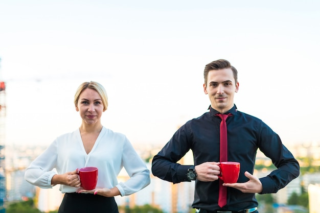 Casal de empresários, homem morena atraente e mulher bonita loira ficar no telhado e beber café