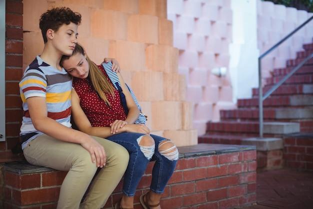Casal de escola chateado sentado perto da escada