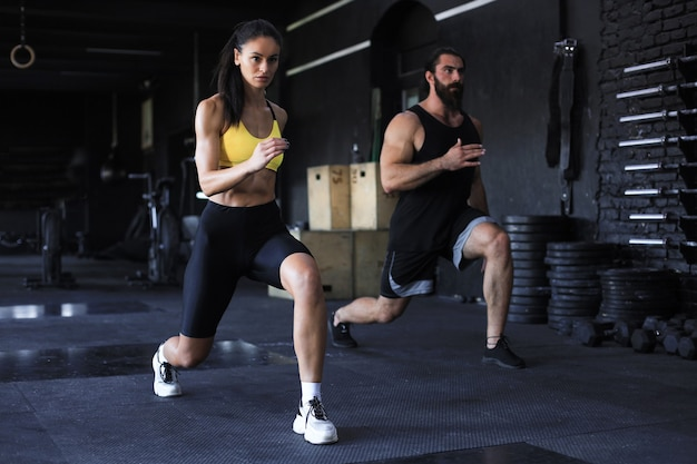 Casal de esporte atraente fazendo fitness no ginásio.