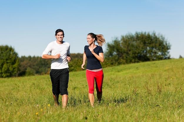 Casal de esporte, movimentando-se no prado