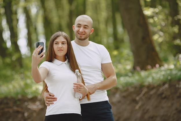 Casal de esporte passa o tempo em uma floresta de verão