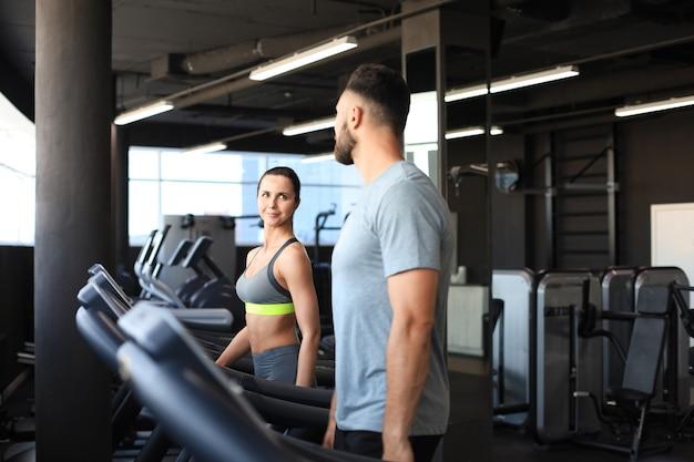 Casal de esporte saudável correndo em uma esteira em um ginásio de esportes.