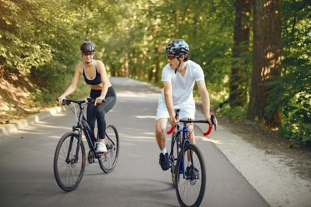 Casal de esportes andando de bicicleta na floresta de verão