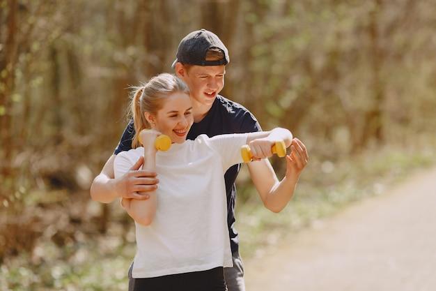 Casal de esportes treinando em uma floresta de verão