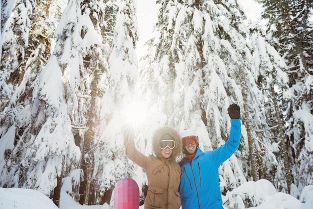 Casal de esquiadores acenando com as mãos